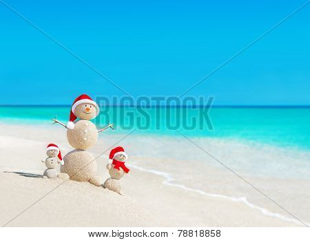 Snowmen Family At Tropical Beach In Santa Hats. New Years And Christmas Concept