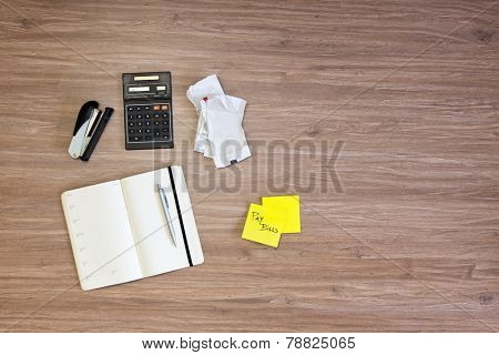 Background of various desktop items on a wooden surface. Items include a stapler, calendar, pen, calculator, some wrinkled bills, and a sticky note with the text Pay Bills written on one of the sheets