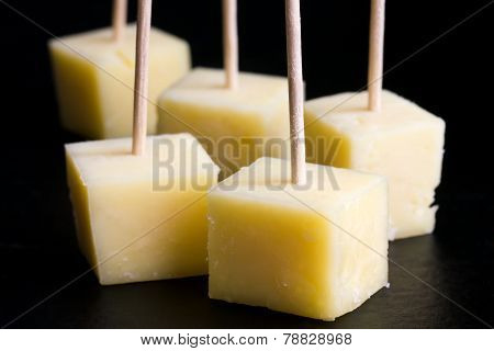 Cubes of yellow cheese on toothpicks.