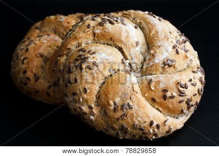 Whole wheat kaiser rolls with sesame seeds on black surface