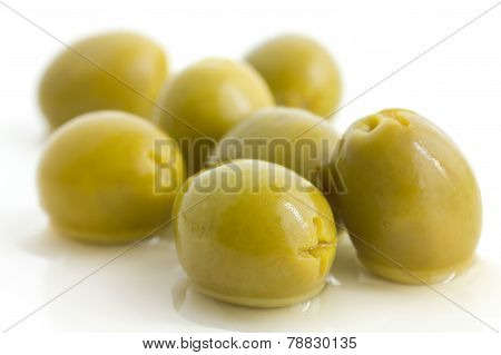 Pitted green olives with brine on white