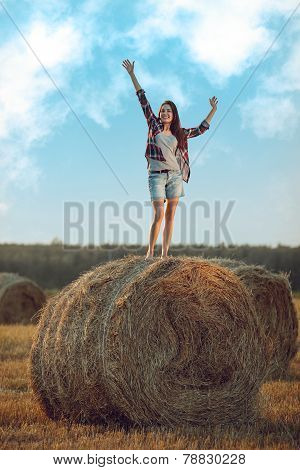 Happy Woman Standing On Haystack
