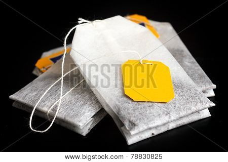 Tagged teabags with string on black surface.
