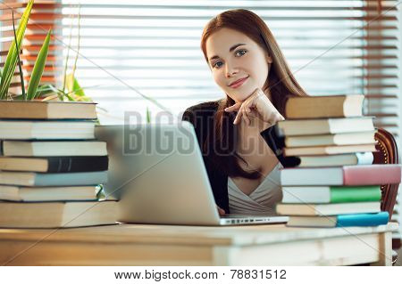 Girl with laptop and books