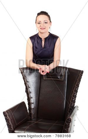 Young Beautiful Business Woman Behind Armchair In Studio. Isolated On White Background