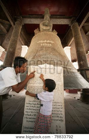 Father And Son Reading Label Of Mingun Bell In Myanmar.