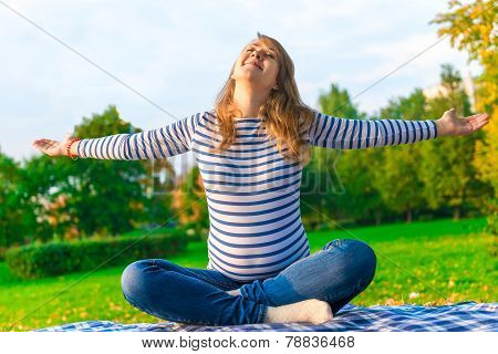 Pregnant Girl Is Preparing For The Birth. Doing Breathing Exercises On The Nature