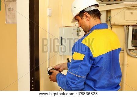 Electrician stripping electrical wires  wall socket
