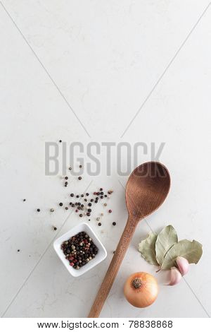 Wooden spoon with bay leaves, garlic bulbs and small bowl of pepper corns
