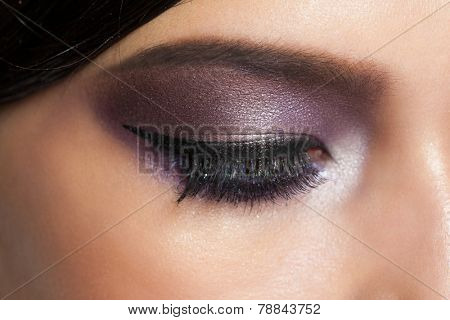 Closeup image of closed woman eyes with beautiful bright makeup. Makeup with eyeliner and falce eyelashes