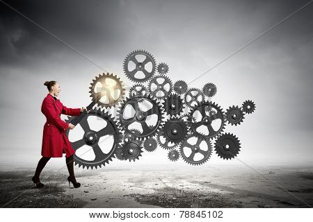 Young woman in red coat fixing mechanism with wrench