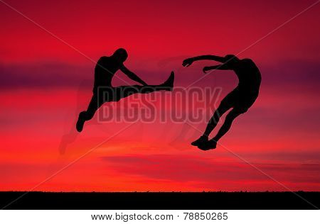 Silhouettes Of Two Fighters On Sunset Fiery Background. Battle At Sunset. Kick In The Air At The Opp