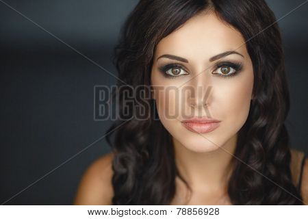 portrait of a serious lady with beautiful makeup over dark background