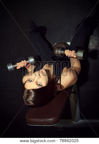 Brutal Athletic Woman Pumping Up Muscules With Dumbbells In The Darkness