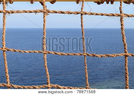 view of the sea through a network of coconut ropes