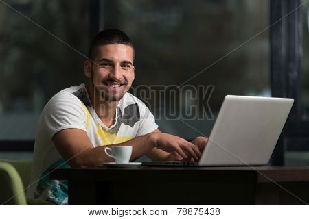 Happy Male Student In Cafe With Laptop