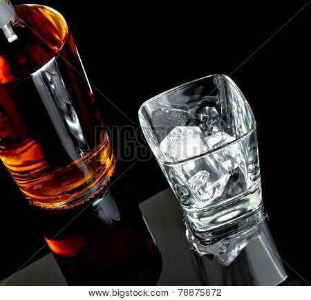 Top Of View Of Empty Whiskey Glass With Ice Near Bottle On Black Background