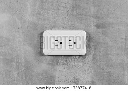 Socket, electrical outlet on gray wall. Close-up image.