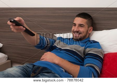 Male Student On Bed With Remote Control
