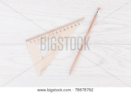 Triangle Ruler And Pencil On Wooden Background