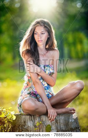 Young beautiful long hair woman wearing a multicolored dress posing on a stump in a green forest