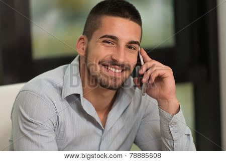Happy Young Man In Library Using Phone