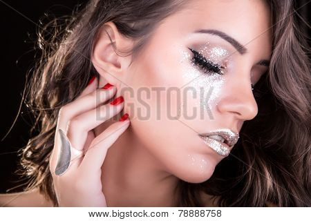 Gorgeous silver glitter make up on eyes and lips, beautiful brunette woman with medium length hair