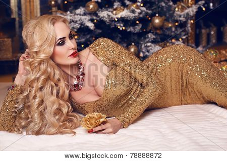 Woman With Blond Hair In Luxurious  Dress Posing Beside A Christmas Tree