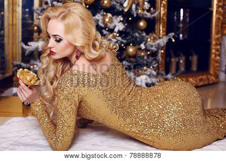 Woman With Blond Hair In Luxurious Golden Dress Posing Beside A Christmas Tree