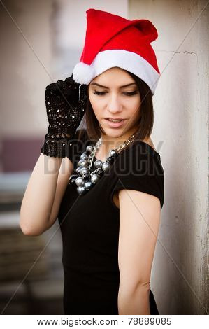 Christmas Santa hat outdoors woman portrait.Sexy seductive woman wearing her Santa hat with urban ba