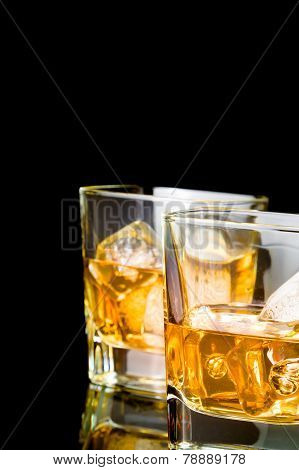 Whiskey With Ice In Glasses On Black Background