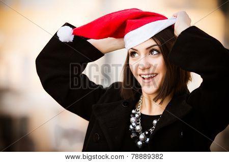 Christmas Santa hat outdoors woman portrait.Sexy seductive woman wearing her Santa hat with urban ba