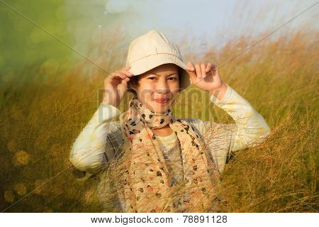 Young Woman Is Standing In Meadow With Raised Arms Enjoying Sunlight
