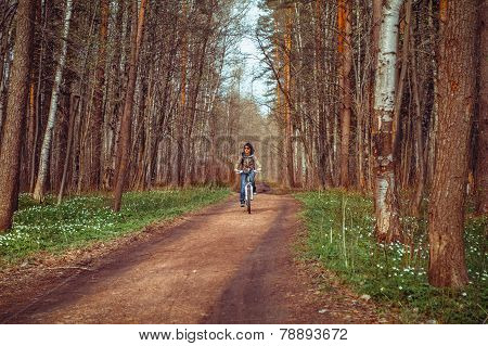Woman cycling on path in forest