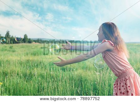 Girl Playing Among Soap Bubbles In Summer