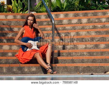 The girl with guitar is sitting on the steps