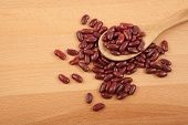 stock photo of kidney beans  - Red kidney beans with wooden spoon on wood table - JPG