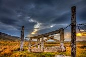 picture of iceland farm  - Dilapidated gate on a farm in Iceland with dramatic evening sky in the background - JPG