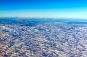 stock photo of stratus  - view colored clouds from an airplane at dawn - JPG