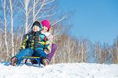 stock photo of sled  - Two cute kids riding sled and having fun - JPG