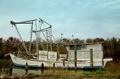 pic of bayou  - shrimp boat with large nets on water by pilings - JPG