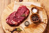 stock photo of ribeye steak  - Raw fresh meat Ribeye Steak with salt and pepper on wooden background - JPG