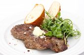 picture of rib eye steak  - Perfect roast pork rib eye steak with baguette and simple salad topped with melting butter - JPG