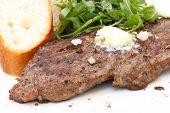 stock photo of rib eye steak  - Perfect roast pork rib eye steak with baguette and simple salad topped with melting butter - JPG