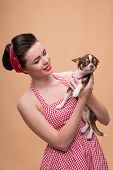 picture of headband  - Portrait of pretty brunette  girl in rose dress and red headband   in retro style  with Chihuahua smiling waist up - JPG