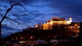picture of brighten  - Late evening panorama view of Spilberk Castle in Brno with a tree branch in one corner and dark clouds in another one - JPG