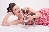 picture of headband  - Pretty brunette  girl in rose dress and red headband in retro style  lying with Chihuahua waist up isolated on white background - JPG