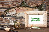 pic of musky  - Reel and lure on table with fish in background - JPG