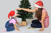 stock photo of conifers  - Sisters decorate a new - JPG