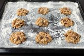 foto of baked raisin cookies  - uncooked oatmeal cookies with raisins on baking tray - JPG